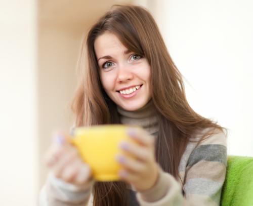 uśmiechnięta kobieta z żółtą filiżanką