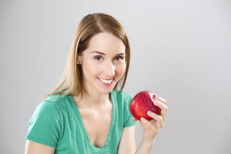 Uśmiechnięta kobieta z jabłkiem